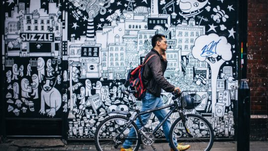 Man met fiets voor muur